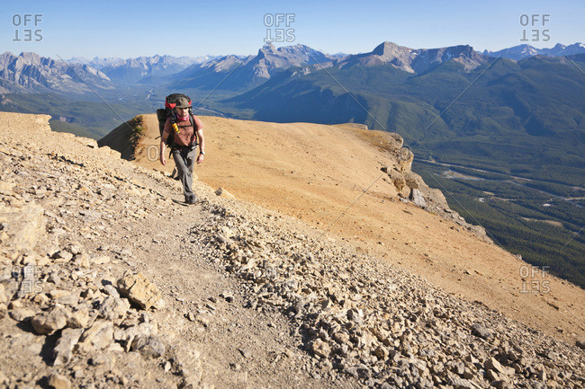 A man is hiking on Castle Mountain, Banff National Park, Alberta, Canada.