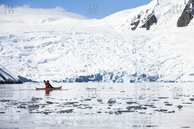 A man is paddling a sea kayak in Graham Passage, Antarctic Peninsula, Antarctica.