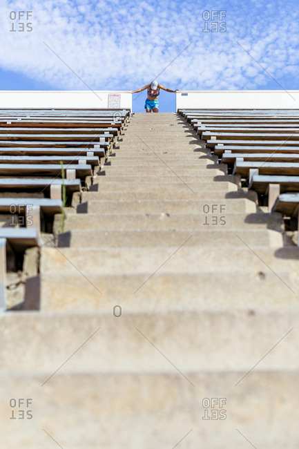 Woman bending forward on top of steps in stadium