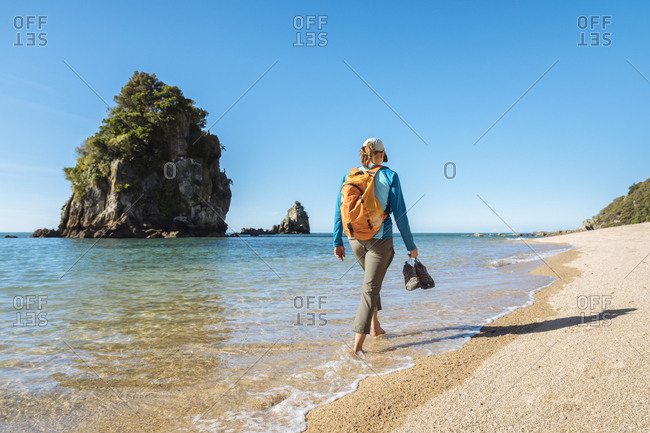 Woman walking barefoot along coastline of Abel Tasman National Park