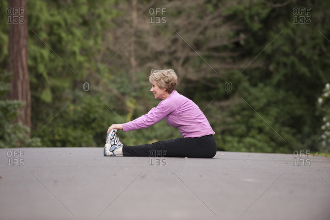 A middle aged  woman exercising in a city park.