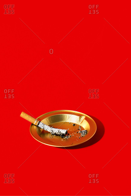An extinguished cigarette in a golden ashtray, on a red background