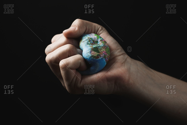 Closeup of a young caucasian man smashing a world globe in his hand