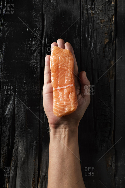 High angle view of a caucasian man with a piece of raw salmon in his hand