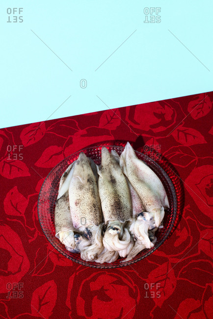 Some raw cuttlefishes in a glass plate, placed on a red flower-patterned tablecloth