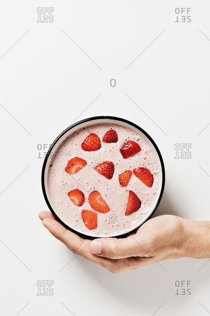 High angle view of a caucasian man with a pink smoothie topped with pieces of strawberry