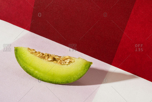 Closeup of a slice of galia melon on a white and red background