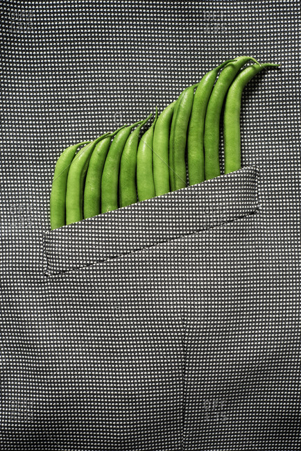 Some raw green beans peeking out from the pocket of a formal jacket