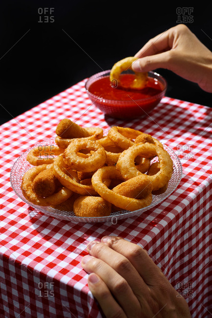 Caucasian man dipping in ketchup a spanish calamares a la romana, a battered and deep-fried squid ring