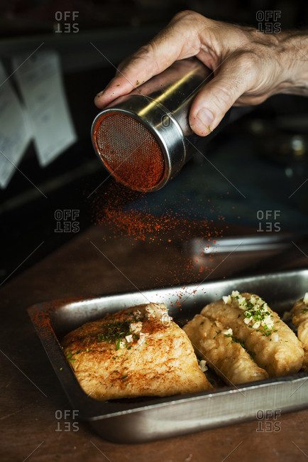 Closeup of a caucasian man sprinkling paprika on some battered and fried pieces of codfish