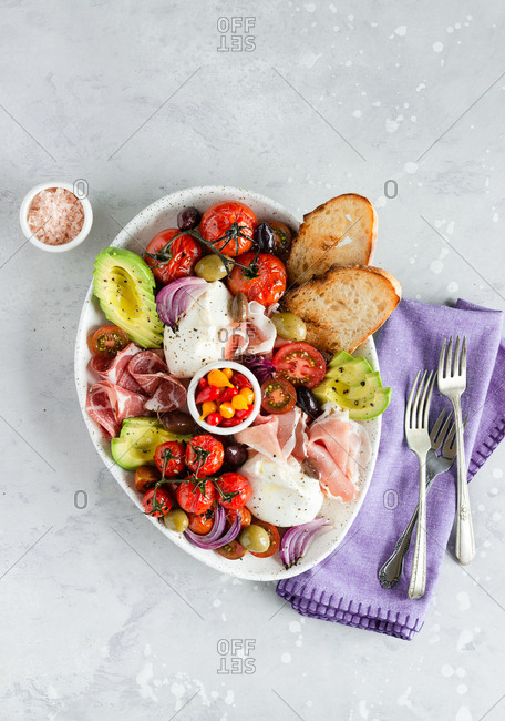 Fresh burrata cheese with baked and fresh tomatoes, avocado, pickled peppers and charcuterie meat antipasto plate top view