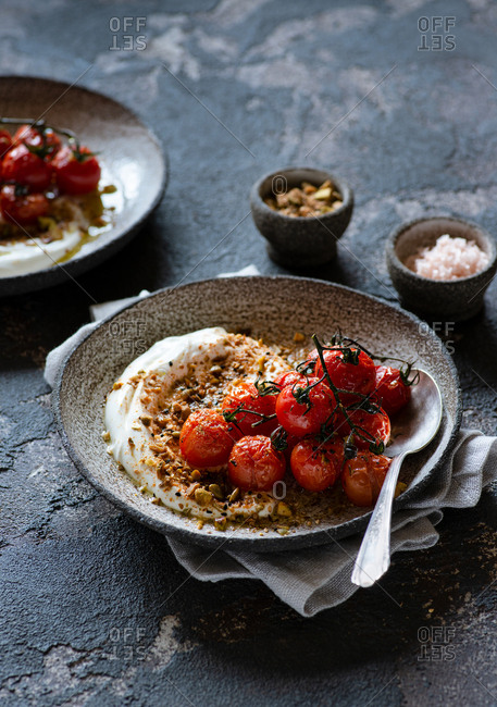 Baked tomatoes with greek yogurt and dukkah served on rustic plates
