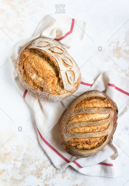Loaves of freshly baked homemade sourdough bread on light background top view