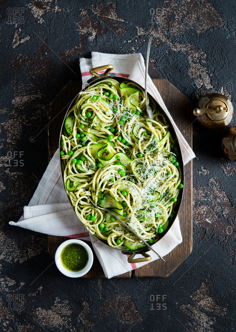Spaghetti with peas zucchini and pesto sauce in a vintage pot over dark background top view