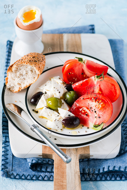 Breakfast with heirloom tomatoes, feta cheese, olives and soft-boiled egg served with crusty multigrain bread
