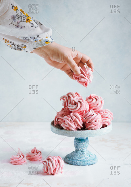 Woman's hand putting or taking pink cranberry meringues or zefir or marshmallow cake stand