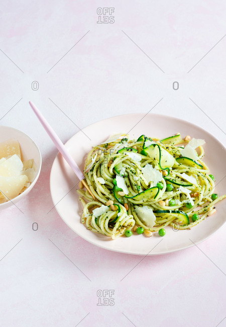 Spaghetti with peas, zucchini, pine nuts, cheese and pesto sauce in a plate over pink background