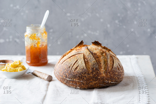 Crusty loaf of sourdough bread with jar of orange jam and butter over rustic napkin