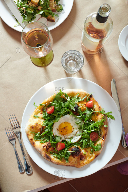Stone fired oven flat bread pizza with arugula, cherry tomatoes and a fried egg on top