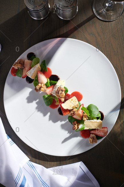 A composed salad of strawberries, walnuts, brie, balsamic reduction, and strawberry puree presented on a white plate at a restaurant outdoors in the afternoon light.