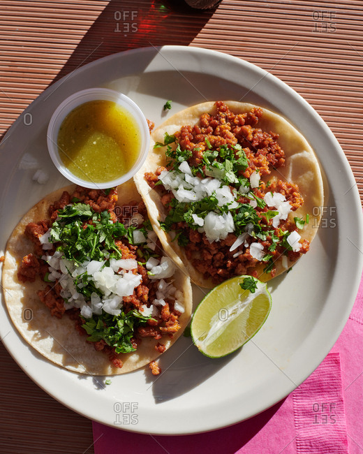 Chorizo tacos served outdoors at a small stand with onions, cilantro and tomatillo salsa in the afternoon sun.
