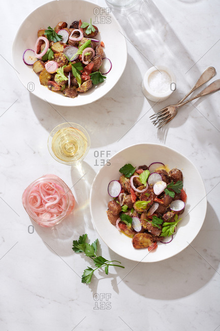 Composed potato salad with celery leaves, pickled shallots, smoked salmon, radishes and red onions, served in two bowls on a marble surface with a glass of white wine nearby