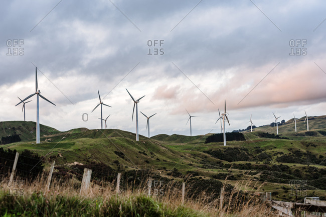Wind turbines along hills at dusk