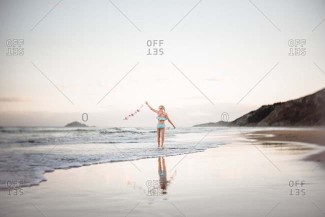 Young girl walking along the beach waving a string of paper hearts