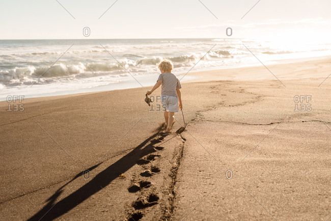 Young boy playing with driftwood on the beach at sunset