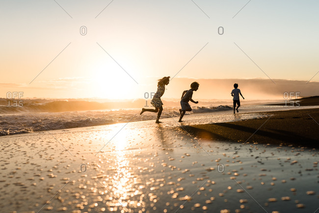 Young girl and boys running along the beach at sunset