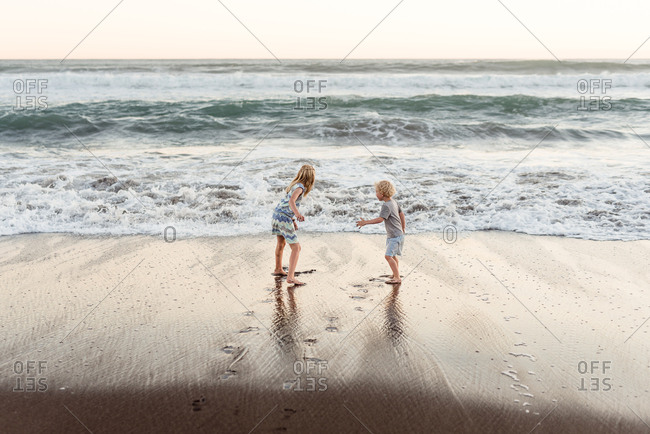 Young brother and sister playing on the beach at dusk