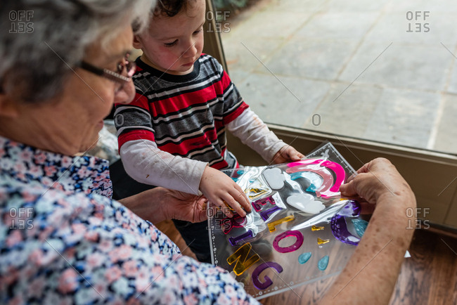 Grandmother helping boy put up window clings