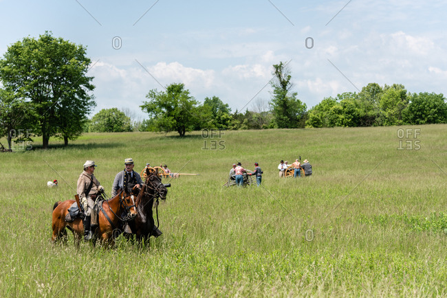 Virginia, USA - May 18, 2019: Men on horses while others shoot cannons during Civil War Reenactment