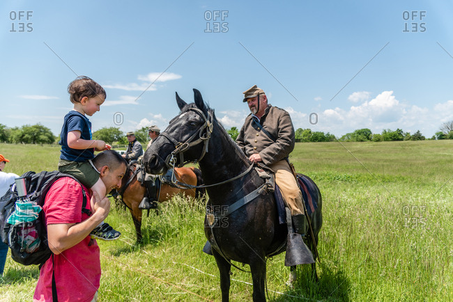 Virginia, USA - May 18, 2019: Father and son looking at soldier on hors during a Civil War Reenactment