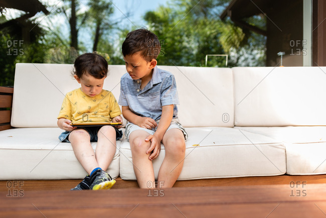 Two little boys sitting on outdoor sofa playing on tablet