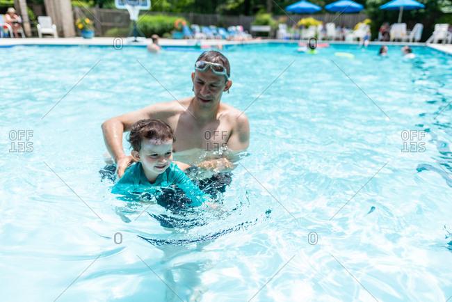 Father teaching toddler boy to swim