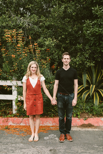Couple holding hands in front of flowers and plants