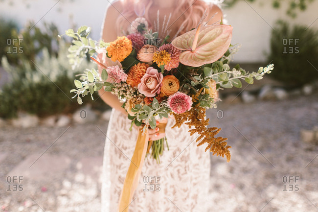 Bride holding colorful pink and orange bouquet