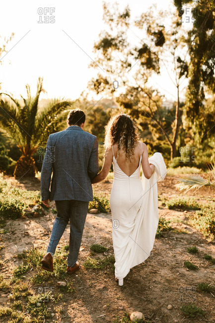 Rear view of bride and groom walking together outdoors
