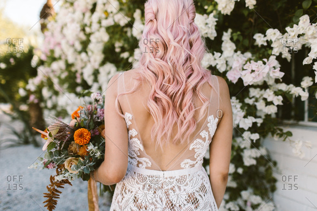 Bride with pink hair holding colorful pink and orange bouquet