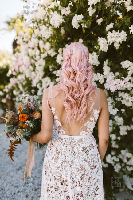 Bride with pink hair holding colorful bouquet in front of a flower wall
