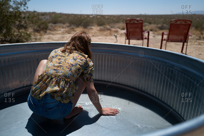 Woman filling metal water basin