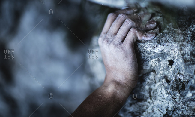 Hand on cliff during mountain climb