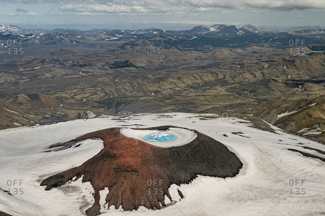 Aerial view of a volcanic crater in the area of Thorsmork, Iceland. With the snow melting as the season turns into summer, glacier ice like this give off the most brilliant deep blue.