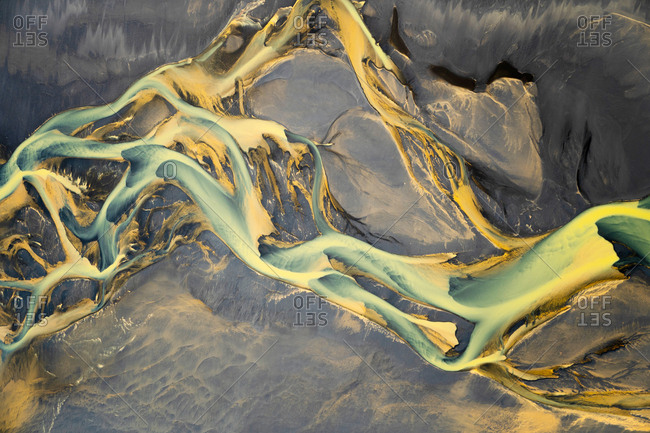 Aerial view of a volcanic river just outside of Villingholt, Iceland. Rivers like this are all over the Icelandic landscape, with colors ranging from yellow to blue to green.