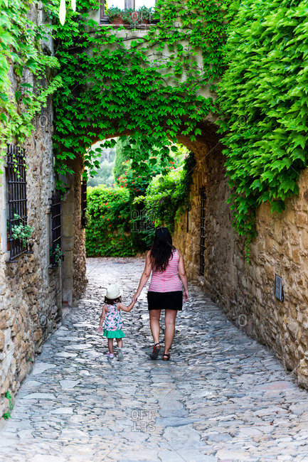 Mother and little girl visiting Europe in summer, walking holding hands in the medieval village of Peratallada, Girona, Spain