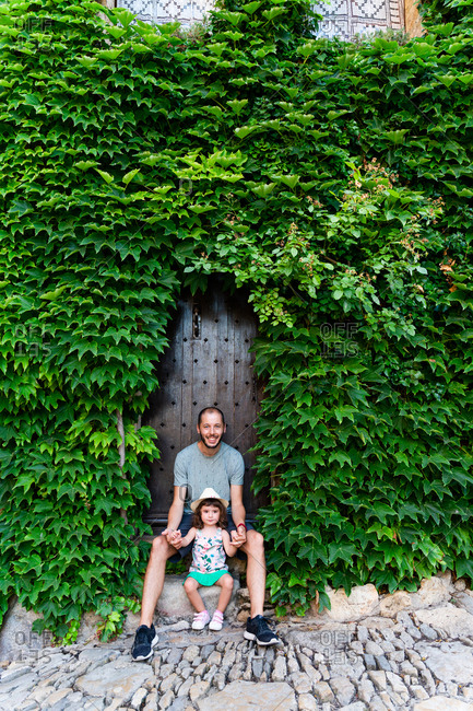 Father and little girl visiting Europe in summer, sitting next to a house covered by ivy. Peratallada, Girona, Spain