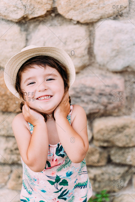 Happy little girl holding straw hat with a big smile in summer