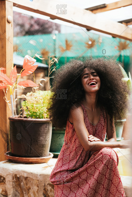 Dark skinned woman portrait with big afro curly hair in a comfortable dress, natural beauty concept