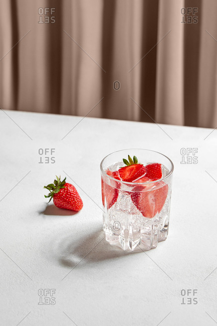 Strawberry infused water with ice cubes in crystal glass composed on white table against drapery